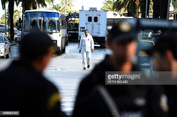 Tunisian forensic police inspect the wreckage of a bus the day after bomb attack on the vehicle which was transporting Tunisia's presidential guards...