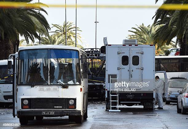 Tunisian forensic police inspect the wreckage of a bus the day after a bomb attack on the vehicle which was transporting Tunisia's presidential...