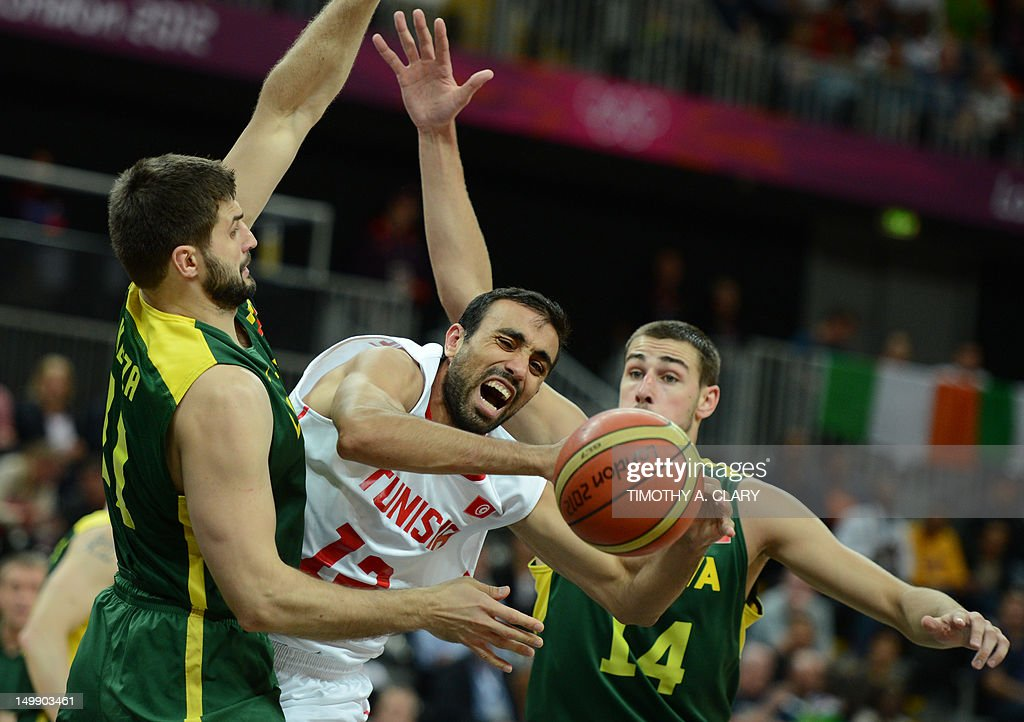 Tunisian forward Makram Ben Romdhane (C) vies with Lithuanian forward Linas Kleiza (L) and Lithuanian centre Jonas Valanciunas (R) during the Men's Basketball Preliminary round match Tunisia vs. Lithuania as part of the London 2012 Olympic Games at the Basketball Arena on August 6, 2012 in London, England.
