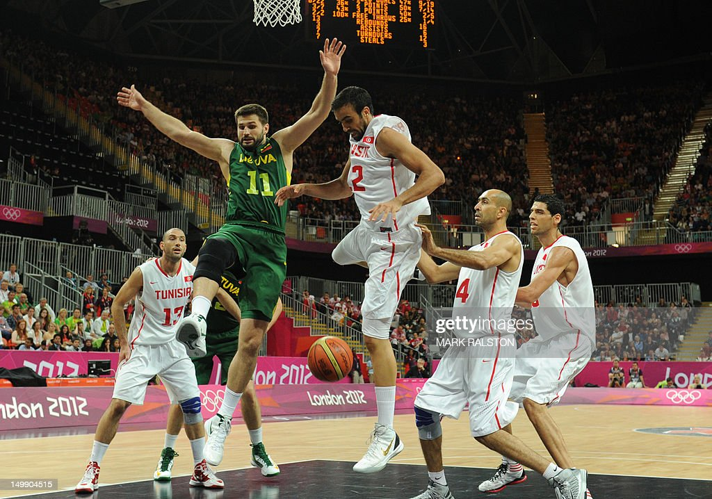 Tunisian forward Makram Ben Romdhane (C) vies with Lithuanian forward Linas Kleiza (2ndL) during the Men's Basketball Preliminary round match Tunisia vs. Lithuania as part of the London 2012 Olympic Games at the Basketball Arena on August 6, 2012 in London, England