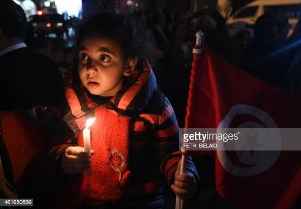 A Tunisian girl holding her national flag takes part in a candlelight vigil in Tunis on January 17 in tribute to Tunisian national Yoav Hattab one of...