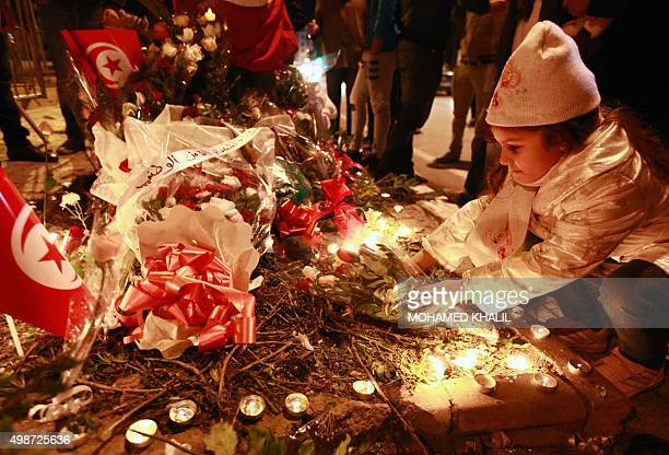 A Tunisian girl places flowers during a candle vigil on November 25 2015 at the site of the attack on a bus in central Tunis which killed several...