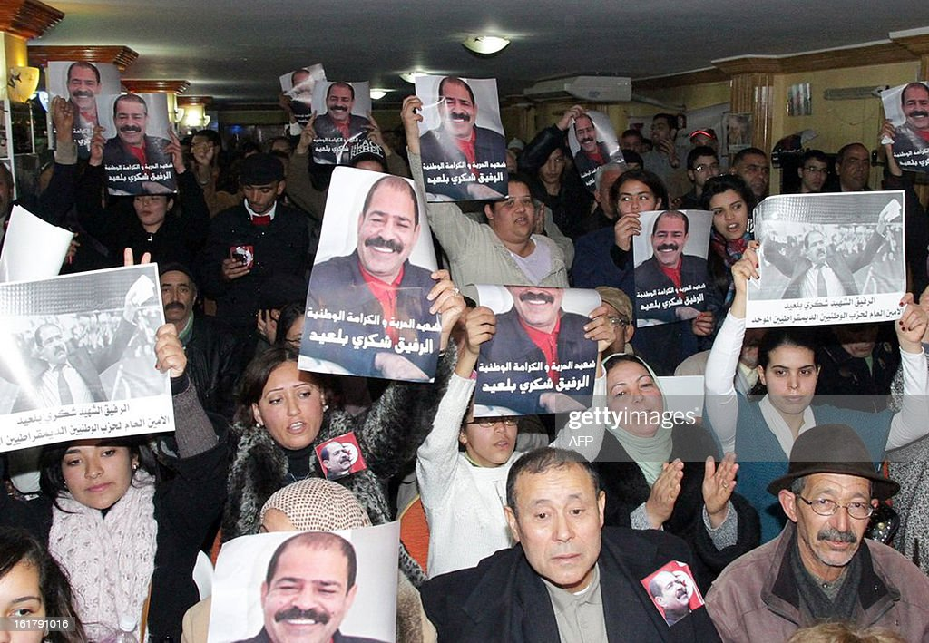 Tunisian hold portraits of murdered opposition figure Chokri Belaid during a meeting in his memory with his widow and representatives of the Tunisia's leftist opposition alliance, Front Populaire on February 16, 2013 in Belaid's hometown Jandouba, northwestern Tunisia.