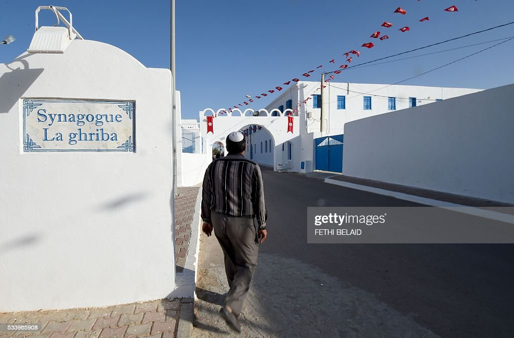 A Tunisian Jew walks in front of the Ghriba Synagogue, thought to be Africa's oldest synagogue, on May 24, 2016 one day before the Jewish annual pilgrimage in Djerba. This week marks the 14th anniversary of the suicide bombing that racked this sleepy island resort, desecrating an ancient synagogue and killing 21 people. / AFP / FETHI
