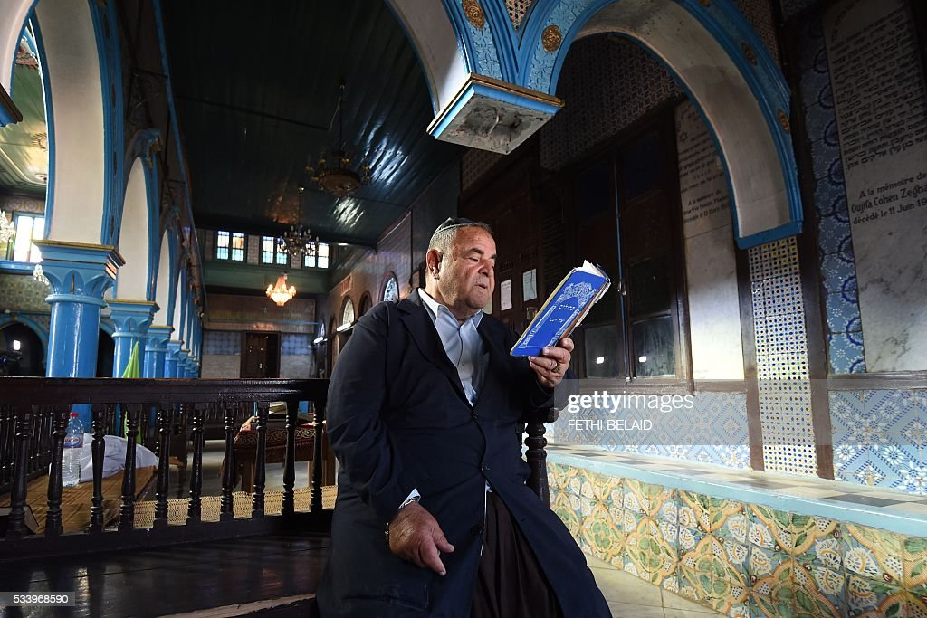 Tunisian Jewish Perez Trabelsi, President of the Jewish community of Djerba reads the Torah, Judaisms most important text, at the Ghriba synagogue on the Tunisian resort island of Djerba one day before the start of a two-day annual pilgrimage, on May 24, 2016. Pilgrims arrived at Tunisia's Ghriba synagogue, the oldest in Africa, expressing hope that this year would mark a turning point for the ritual despite a rise in Islamist unrest since the 2011 revolution. / AFP / FETHI