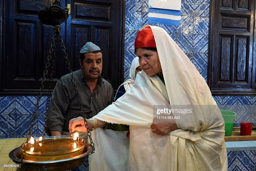 A Tunisian Jewish woman lights a candle at the Ghriba synagogue on the Tunisian resort island of Djerba during the annual Jewish pilgrimage on May 25, 2016. Pilgrims arrived at Tunisia's Ghriba synagogue, the oldest in Africa, expressing hope that this year would mark a turning point for the ritual despite a rise in Islamist unrest since the 2011 revolution. Djerba is home to one of the last Jewish communities in the Arab world. / AFP / FETHI