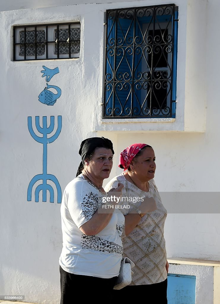 Tunisian Jewish women walk in the village of Hara Kebira on the Tunisian resort island of Djerba one day before the start of a two-day annual pilgrimage, on May 24, 2016. Pilgrims arrived at Tunisia's Ghriba synagogue, the oldest in Africa, expressing hope that this year would mark a turning point for the ritual despite a rise in Islamist unrest since the 2011 revolution. / AFP / FETHI