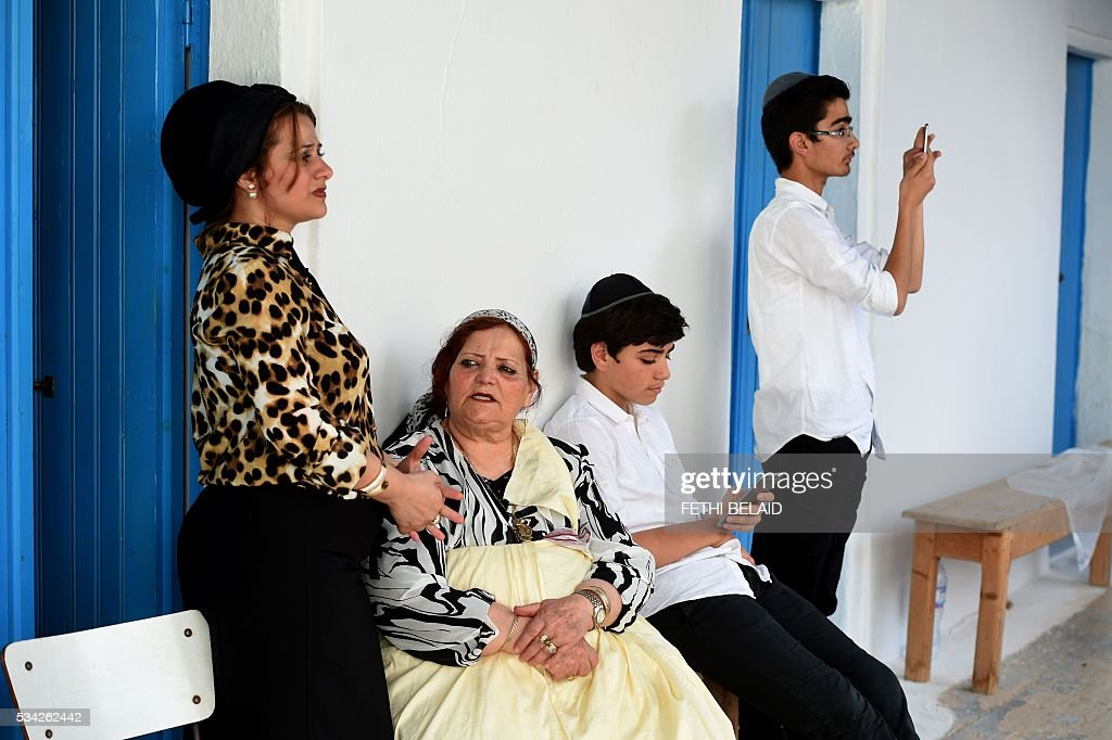 Tunisian Jews from the Trabelsi family wait outside the Ghriba synagogue on the Tunisian resort island of Djerba during the annual Jewish pilgrimage on May 25, 2016. Pilgrims arrived at Tunisia's Ghriba synagogue, the oldest in Africa, expressing hope that this year would mark a turning point for the ritual despite a rise in Islamist unrest since the 2011 revolution. Djerba is home to one of the last Jewish communities in the Arab world. / AFP / FETHI