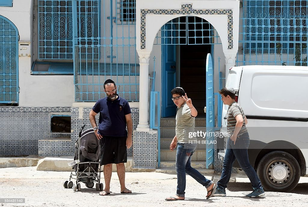 Tunisian Jews walk in the streets of Hara Kebira, the main jewish quarter of the Tunisian resort island of Djerba, after attending a ceremony at the Ghriba synagogue during the annual Jewish pilgrimage on May 26, 2016. Jewish pilgrims arrived in Djerba the previous day for their annual two-day pilgrimage at Tunisia's Ghriba synagogue, the oldest in Africa. / AFP / FETHI