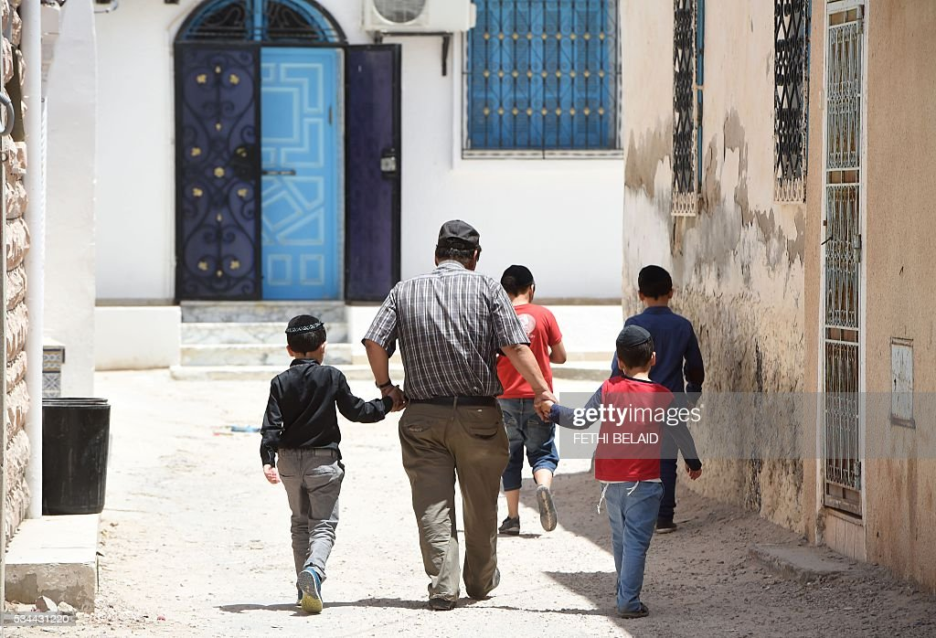 Tunisian Jews walk in the streets of Hara Kebira, the main jewish quarter of the Tunisian resort island of Djerba, after attending a ceremony at the Ghriba synagogue on the during the annual Jewish pilgrimage on May 26, 2016. Jewish pilgrims arrived in Djerba the previous day for their annual two-day pilgrimage at Tunisia's Ghriba synagogue, the oldest in Africa. / AFP / FETHI