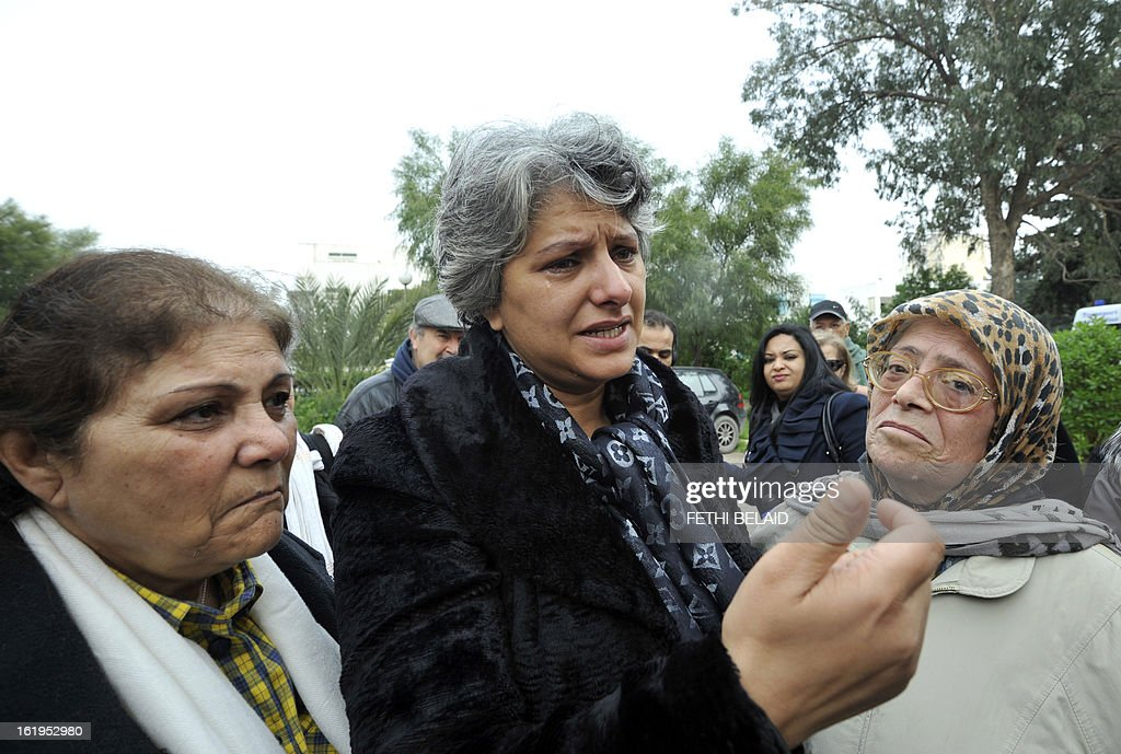 Tunisian journalist and human rigth defender Om Zied (L) stands next to the widow of murdered opposition figure Chokri Belaid, Besma Khalfaoui, as she speaks while standing close to the vandalised and broken statue erected in his honour, on February 18, 2013, in Tunis. The memorial, installed as a work of contemporary art by Tunisian artists, was ripped off from its base and broken, and the flowers surrounding it were trampled and scattered. Belaid, a leftist leader and fierce critic of Tunisia's ruling Islamist-led government, was shot dead by a gunman as he left his home. is seen left.