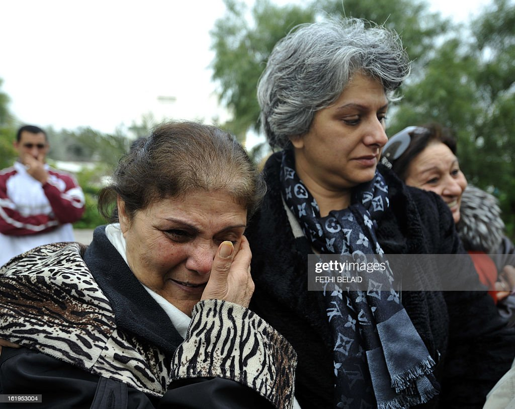 Tunisian journalist and human rigth defender Om Zied (L) weeps as she stands next to the widow of murdered opposition figure Chokri Belaid, Besma Khalfaoui, as they look at the vandalised and broken statue erected in his honour, on February 18, 2013, in Tunis. The memorial, installed as a work of contemporary art by Tunisian artists, was ripped off from its base and broken, and the flowers surrounding it were trampled and scattered. Belaid, a leftist leader and fierce critic of Tunisia's ruling Islamist-led government, was shot dead by a gunman as he left his home. is seen left.