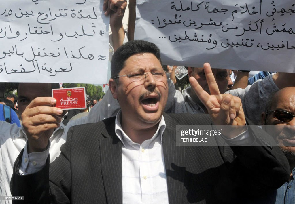 A Tunisian journalist shows his press card flashing the sign of victory during a demonstration against the censorship part of the World Press Freedom Day on May 3, 2013 in Tunis. Protesters accused the Islamist ruling party Ennahda of wanting to exert control over medias.