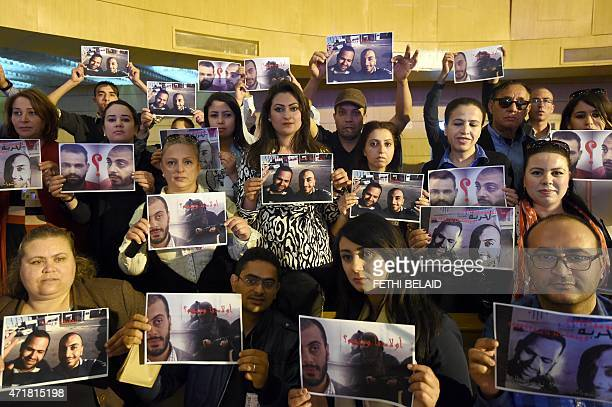 Tunisian journalists hold portraits of Sofiene Chourabi and Nadhir Ktari two of their colleagues who went missing in eastern Libya in September 2014...