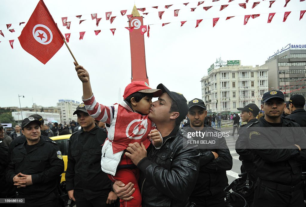 A Tunisian kisses a boy holding a national flag during a gathering as part of the festivities marking the second anniversary of the uprising that ousted long-time dictator Zine El Abidine Ben Ali on January 14, 2013 in Tunis. Tunisians marked two years since the revolution amid a climate of uncertainty marked by social tension, a weak economy, threats from jihadists and a political impasse.