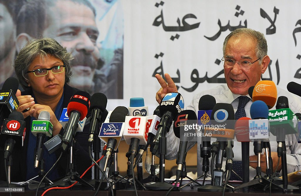 Tunisian lawyer and member of the 'Initiative for the Search for Truth about the Assassination of Chokri Belaid and Mohamed Brahmi' (IRVA), Mokhtar Trifi (R) speaks near Belaid's widow, Basma Khalfaoui during a press conference on November 7, 2013 in Tunis to present new documents related to the assassination of the two opposition politicians. IRVA accused the Tunisian Ministry of Interior of 'hidding' ballistic test results conducted in the Netherlands, which would show that Belaid was assassinated on February 6, 2013 with a gun 'belonging to the Interior Ministry'.