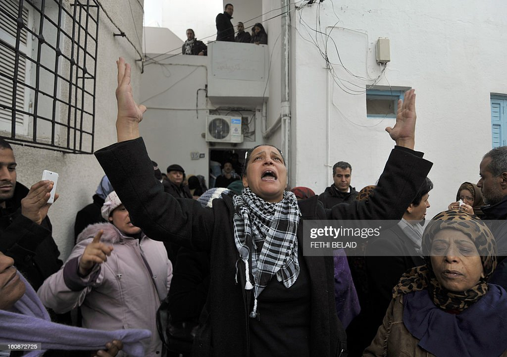 Tunisian lawyer, human rights defender and close friend of the deceased, Leila Ben Debba (C), mourns with friends and relatives on February 7, 2013 in the Tunisian capital's suburb of Jebel Jelloud outside the family home of Chokri Belaid, an outspoken opposition leader who was assassinated the previous day. Police was deployed in force in Tunis amid fears the murder of Belaid could reignite nationwide violence, as the ruling Islamists broke ranks over how to defuse the crisis. Belaid's family said his funeral will take place on February 8 after the main weekly prayers. AFP PHOTO / FETHI BELAID