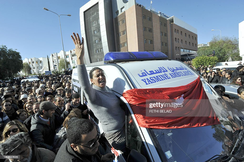 Tunisian lawyer Leila Ben Debba shoots slogans from the window of the ambulance transporting the body of Tunisian opposition leader and outspoken government critic Chokri Belaid, from a clinic in Tunis to the public hospital for an autopsy, after he was shot dead with three bullets fired from close range, on February 6, 2013. Tunisian Premier Hamadi Jebali called the assassination 'an act of terrorism', as the country grapples with growing political instability. AFP PHOTO / FETHI BELAID