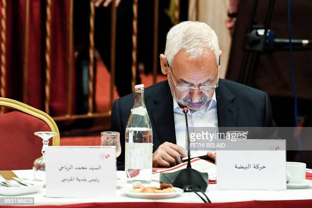 Tunisian leader of Islamist Ennahdha party Rached Ghannouchi looks at a cell phone as he attends a meeting in Gammarth near the capital Tunis with...