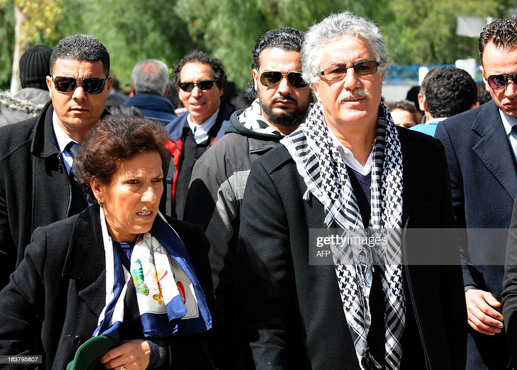 Tunisian leader of Popular Front party Hamma Hammami and his wife Radhia Nasraoui walk towards El-Jellaz cemetery before gathering at the tomb of the anti-Islamist opposition leader Chokri Belaid to mark the 40th day of mourning after his death on March 16, 2013 in a suburb of Tunis. Belaid was gunned down outside his Tunis home on February 6, with the broad daylight killing sparking clashes between protesters and police and prompting the largest anti-government demonstrations since the revolution.AFP PHOTO / SALAH HABIBI