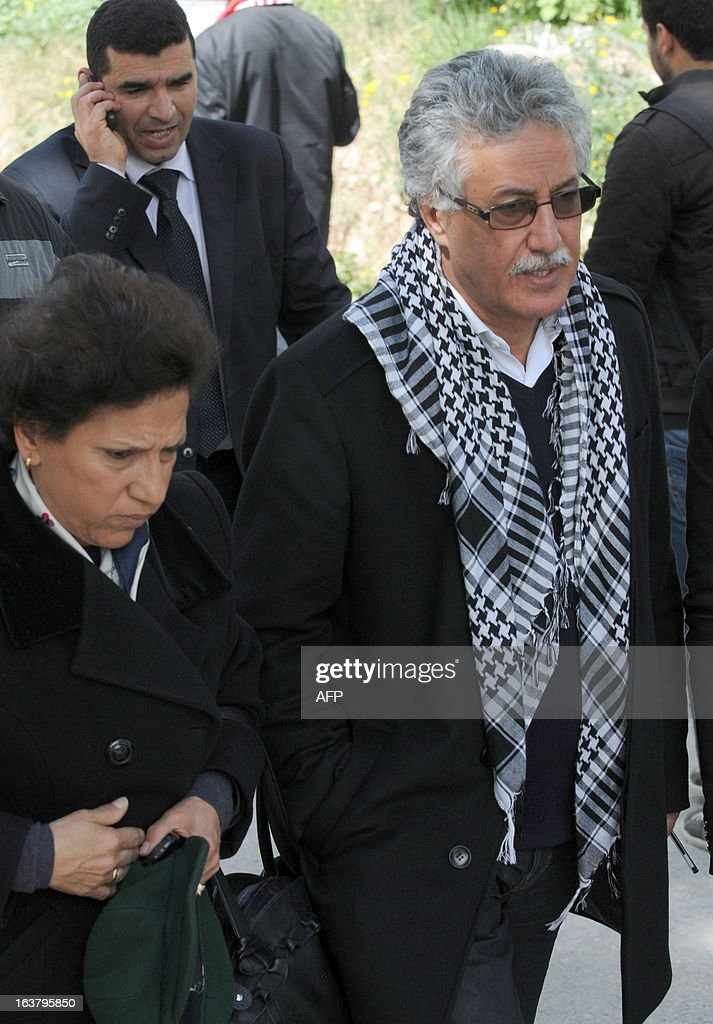 Tunisian leader of Popular Front party Hamma Hammami and his wife Radhia Nasraoui walk towards El-Jellaz cemetery before gathering at the tomb of the anti-Islamist opposition leader Chokri Belaid to mark the 40th day of mourning after his death on March 16, 2013 in a suburb of Tunis. Belaid was gunned down outside his Tunis home on February 6, with the broad daylight killing sparking clashes between protesters and police and prompting the largest anti-government demonstrations since the revolution. AFP PHOTO / SALAH HABIBI