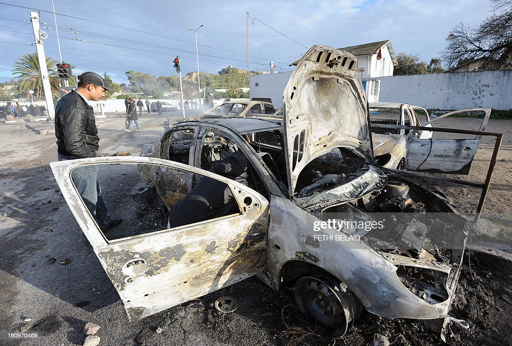 A Tunisian man inspects burnt cars that were set on fire by protesters following the funeral of assassinated opposition leader Chokri Belaid in Tunis on February 8, 2013. Tunisian police fired tear gas and clashed with protesters as tens of thousands joined the funeral of Belaid whose murder plunged the country into new post-revolt turmoil.