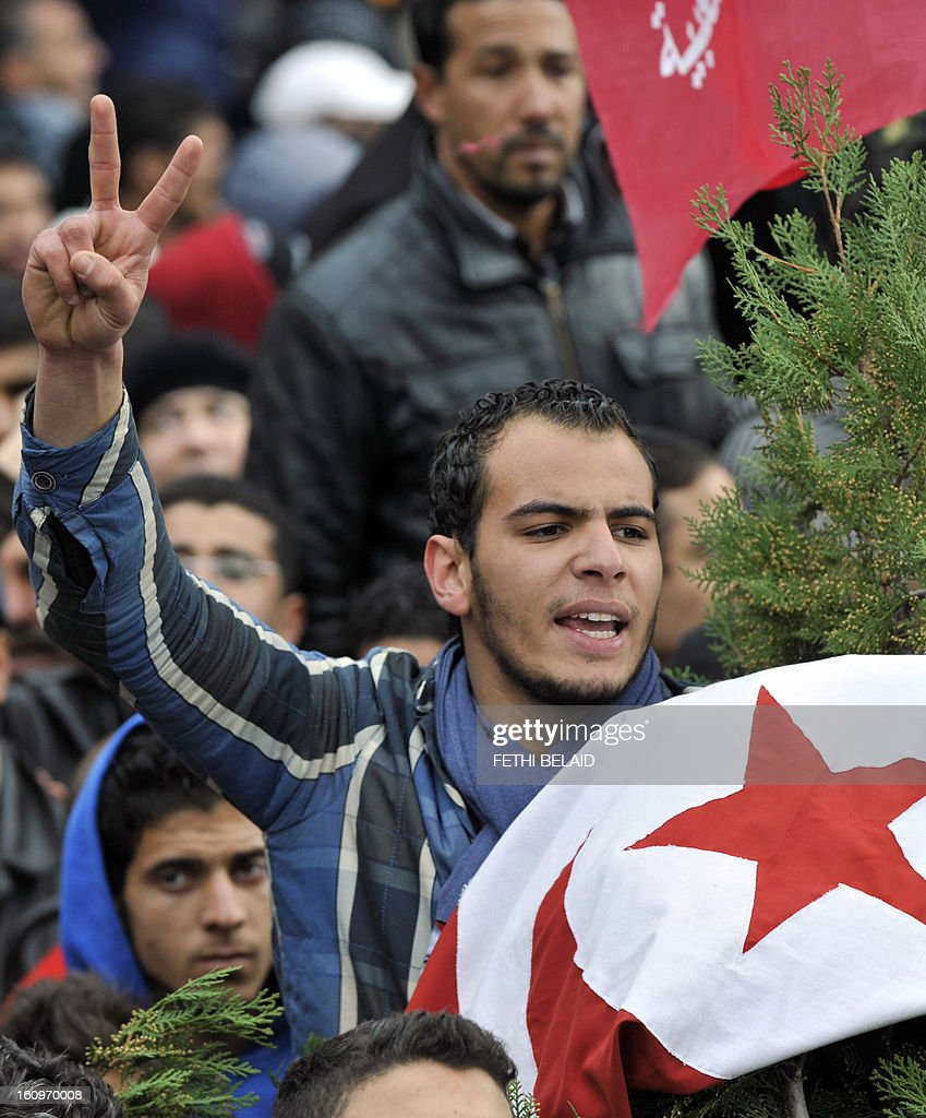 A Tunisian man makes the victory sign while shouting slogans during the burial of assassinated opposition leader Chokri Belaid at El-Jellaz cemetery in a suburb of Tunis on February 8, 2013. Tunisian police fired tear gas and clashed with protesters as tens of thousands joined the funeral of Belaid whose murder plunged the country into new post-revolt turmoil.