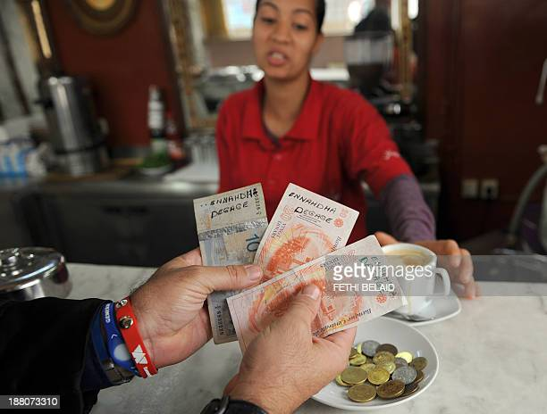 A Tunisian man pays for his coffee with Tunisian dinar bills bearing slogans calling for the Islamist Ennahda party to step down from power at a cafe...