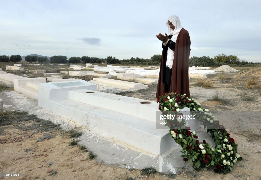 A Tunisian man prays at the mausoleum of Mohamed Bouazizi, the young fruit and vegetable seller whose self-immolation kicked off the Arab Spring in the central town of Sidi Bouzid on December 17, 2012, as Tunisia marks the second anniversary of the start of the revolution. Tunisian President Moncef Marzouki was heckled earlier in the morning, when he visited the grave. / AFP / FETHI