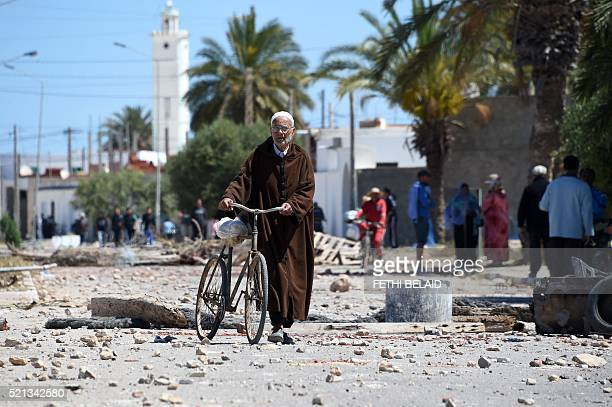 A Tunisian man pushes his biclycle in the locality of Laataya on the island of Kerkennah on April 15 2016 after residents covered the road with...