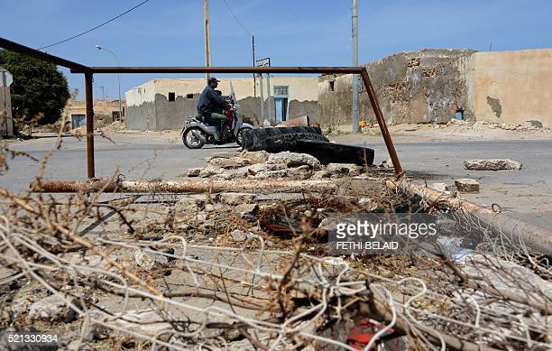 A Tunisian man rides a scooter past a road block set up by residents of the island of Kerkennah during a series of social protests related to...