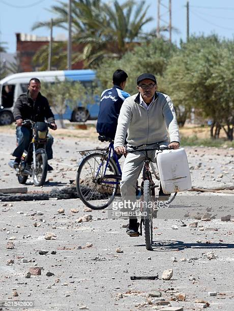 A Tunisian man rides his biclycle in the locality of Laataya on the island of Kerkennah on April 15 2016 after residents covered the road with stones...