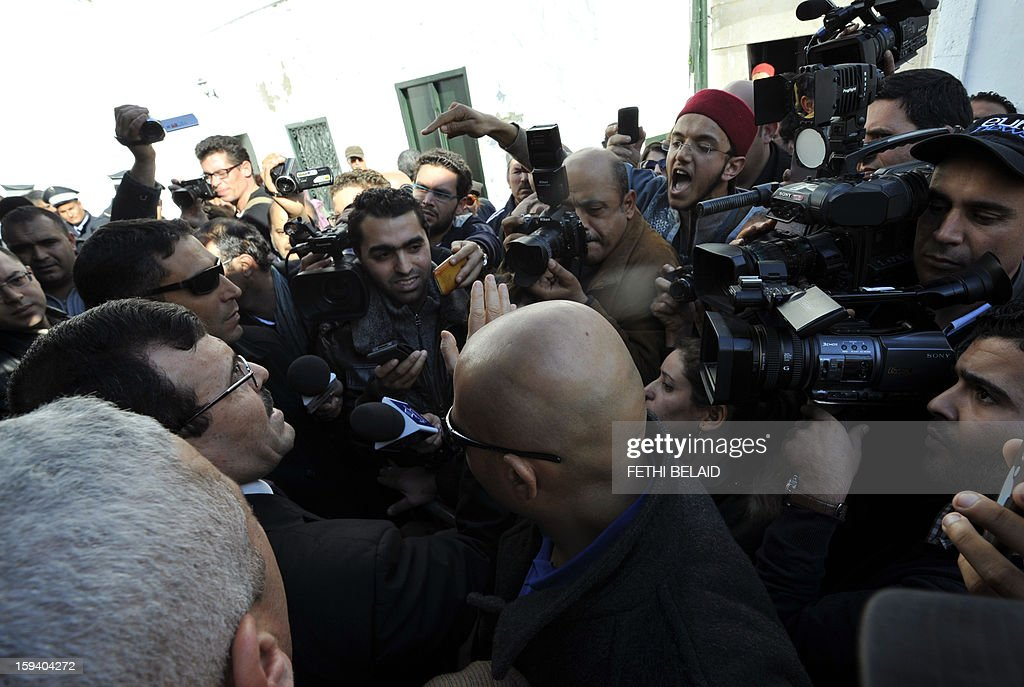 A Tunisian man shouts 'move along' to Interior Minister, Ali Larayedh (L) as he answers journalists' questions outside a mausoleum ravaged by fire in what is thought to have been an arson attack which the presidency denounced as a criminal act on January 13, 2013 in Sidi Bou Said. The residents were angered when Larayedh said: 'This is a criminal act, but it is not up to the police to protect all mausoleums, it is up to the people in charge of these mausoleums.' Several shrines dedicated to Muslim saints have been torched or looted in recent months in Tunisia, in acts blamed on hardline Salafists whose radical version of Sunni Islam does not tolerate saints or shrines. AFP PHOTO /FETHI BELAID