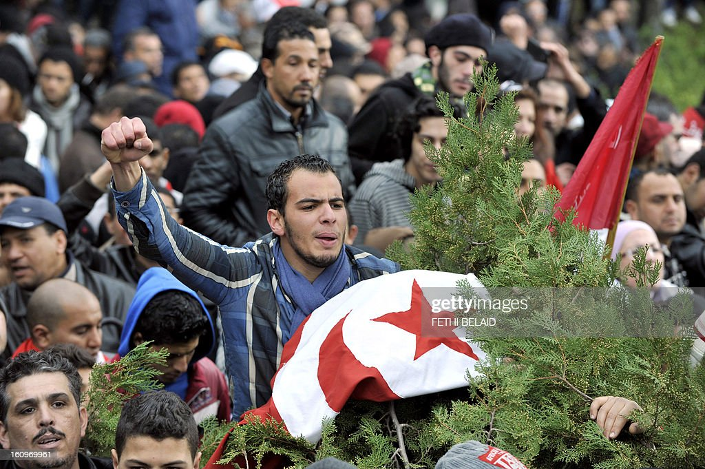 A Tunisian man shouts slogans as mourners gather at El-Jellaz cemetery in a suburb of Tunis for the burial of assassinated opposition leader Chokri Belaid on February 8, 2013. Tunisian police fired tear gas and clashed with protesters as tens of thousands joined the funeral of Belaid whose murder plunged the country into new post-revolt turmoil.