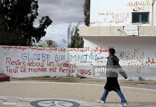 Tunisian man walks past a wall covered in graffiti celebrating the uprising in Tunisia in the town centre of Sidi Bouzid on December 11 where the...