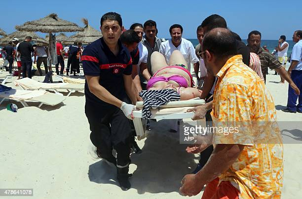 Tunisian medics carry a woman on a stretcher in the resort town of Sousse a popular tourist destination 140 kilometres south of the Tunisian capital...