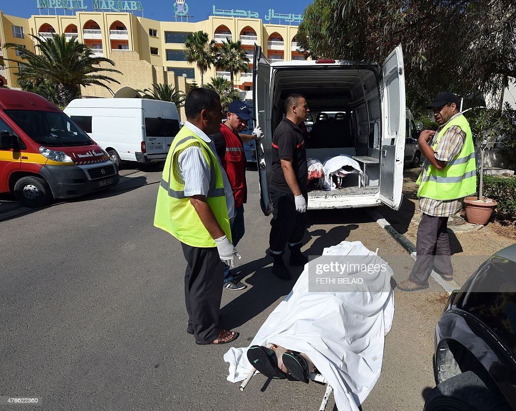 Tunisian medics stand next to the bodies of tourists in the resort town of Sousse a popular tourist destination 140 kilometres south of the Tunisian...