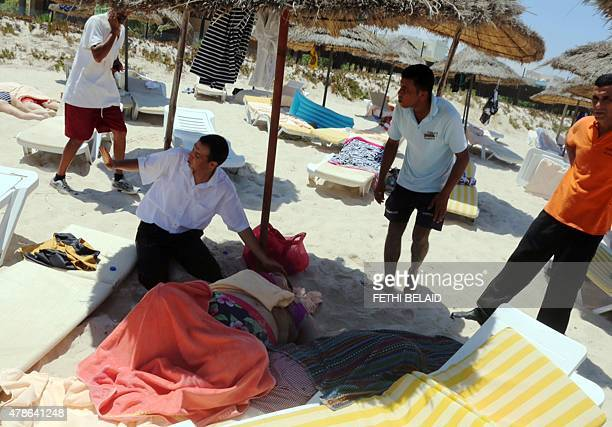 Tunisian men help an injured woman in the resort town of Sousse a popular tourist destination 140 kilometres south of the Tunisian capital on June 26...