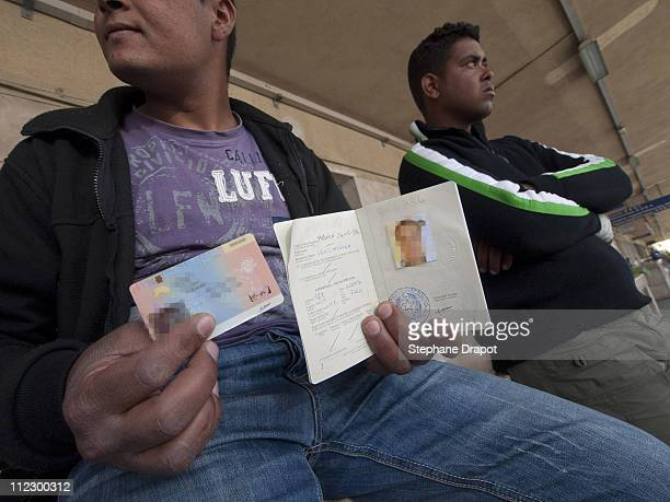 A Tunisian migrant shows his new Italian passport valid for 6 months and a residence permit at Ventimiglia train station before taking his ticket to...