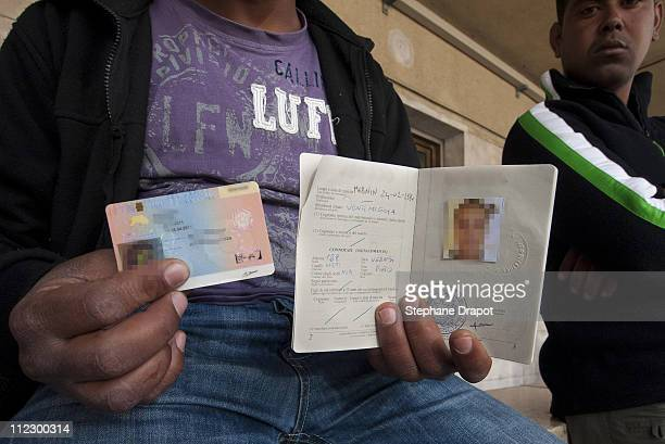 A Tunisian migrant shows his new Italian passport valid for 6 months and a residence permit at the Ventimiglia train station before taking his ticket...