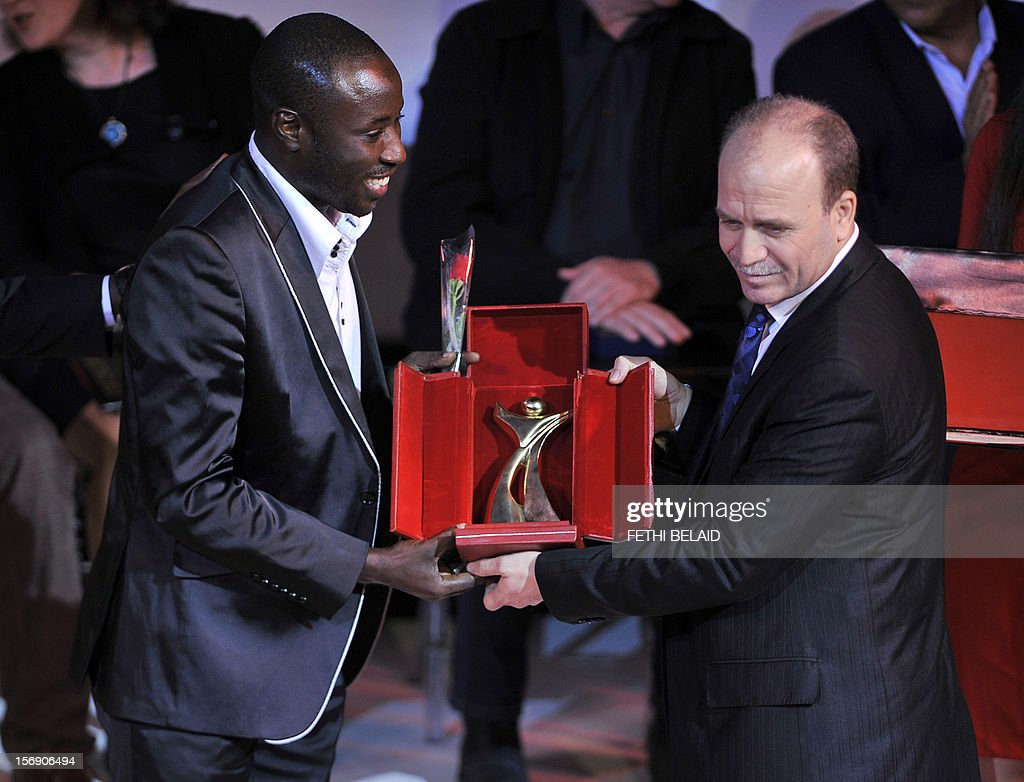 Tunisian Minister of Culture Mehdi Mabrouk (R) presents the Gold Tanit award to Senegalese actor Babacar Oualy for his role in the film 'Pirogue', during the closing ceremony of the 28th edition of the Cinematographic Days of Carthage (JCC) film festival on November 24, 2012, in Tunis.