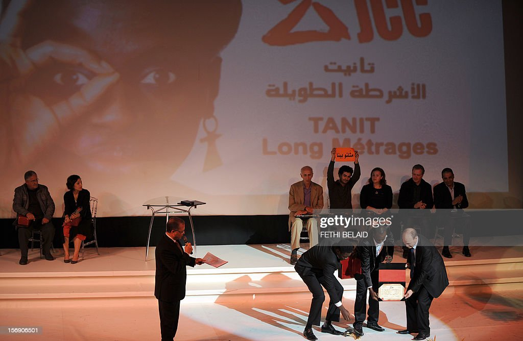 Tunisian Minister of Culture Mehdi Mabrouk (Bottom R) presents the Gold Tanit award to Senegalese actors Babacar Oualy (Bottom 2nd R) and Laity Fall (Bottom 3rd R) for their roles in the film 'Pirogue', during the closing ceremony of the 28th edition of the Cinematographic Days of Carthage (JCC) film festival on November 24, 2012, in Tunis.