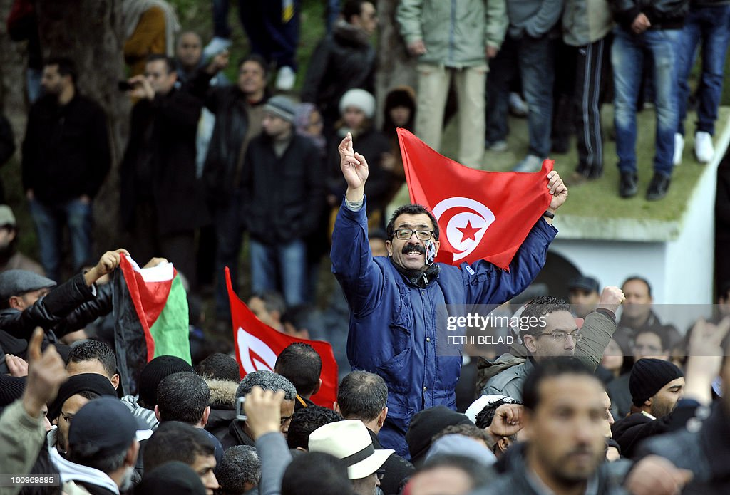 A Tunisian mourner holding his national flag shouts slogans as people gather at El-Jellaz cemetery in a suburb of Tunis for the burial of assassinated opposition leader Chokri Belaid on February 8, 2013. Tunisian police fired tear gas and clashed with protesters as tens of thousands joined the funeral of Belaid whose murder plunged the country into new post-revolt turmoil.