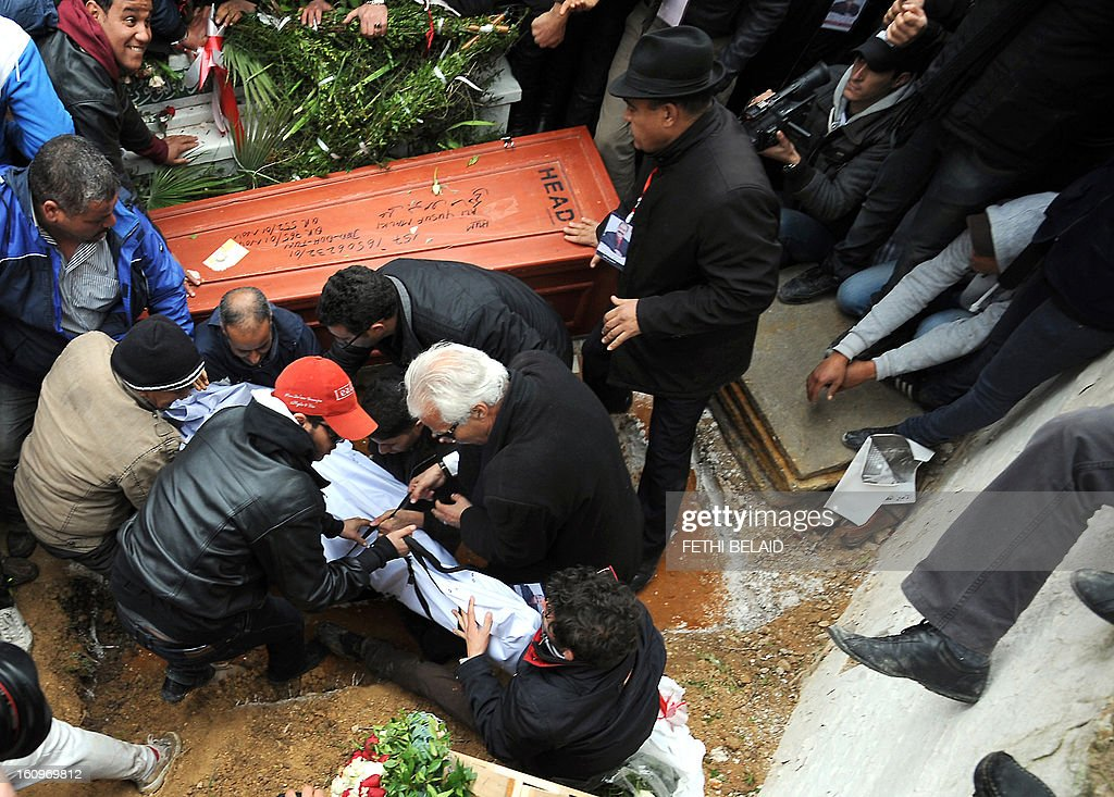 Tunisian mourners bury assassinated opposition leader Chokri Belaid at El-Jellaz cemetery in a suburb of Tunis on February 8, 2013. Tunisian police fired tear gas and clashed with protesters as tens of thousands joined the funeral of Belaid whose murder plunged the country into new post-revolt turmoil.