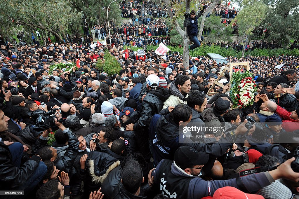 Tunisian mourners gather at El-Jellaz cemetery in a suburb of Tunis for the burial of assassinated opposition leader Chokri Belaid on February 8, 2013. Tunisian police fired tear gas and clashed with protesters as tens of thousands joined the funeral of Belaid whose murder plunged the country into new post-revolt turmoil.