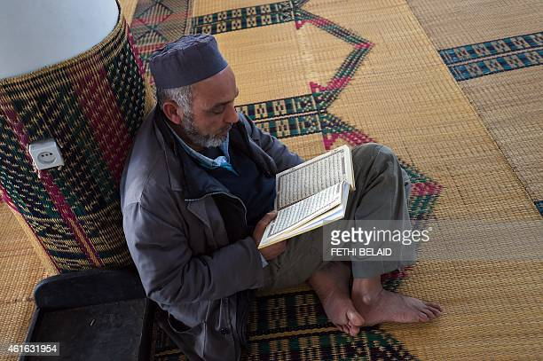 A Tunisian Muslim worshipper reads the Koran Islam's holy book following the Friday prayer at alFath mosque on January 16 2015 in central Tunis Some...