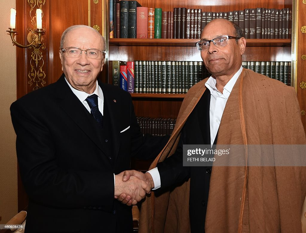 Tunisian newly-elected President <a gi-track='captionPersonalityLinkClicked' href=/galleries/search?phrase=Beji+Caid+Essebsi&family=editorial&specificpeople=998512 ng-click='$event.stopPropagation()'>Beji Caid Essebsi</a> (L) shakes hands with his predecessor <a gi-track='captionPersonalityLinkClicked' href=/galleries/search?phrase=Moncef+Marzouki&family=editorial&specificpeople=2893986 ng-click='$event.stopPropagation()'>Moncef Marzouki</a> during a handover ceremony on December 31, 2014 at the Carthage presidential Palace in Tunis. The election of Essebsi, a veteran of previous regimes, is seen as a landmark for the North African nation, where longtime dictator Zine El Abidine Ben Ali was toppled in 2011. AFP PHOTO / FETHI BELAID
