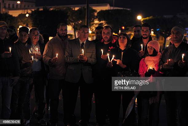 Tunisian Nidaa Tounes party members hold candles during a vigil in Tunis in memory of the victims of a bomb blast earlier in the day on a bus...