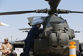 Tunisian officers look at a US Apache helicopter displayed at the Dubai Airshow on November 8 2015 Dubai Airshow took off today to a slow start amid...