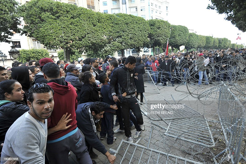 Tunisian people remove fences and barbed wire during a rallye in front of Interior ministry to protest after Tunisian opposition leader and outspoken government critic Chokri Belaid was shot dead with three bullets fired from close range, on February 6, 2013 in Tunis. President Moncef Marzouki denounced the killing of Belaid, an outspoken critic of his government, as an 'odious assassination', while Ennahda chief Rached Ghannouchi told AFP the killers wanted a 'bloodbath' in Tunisia.
